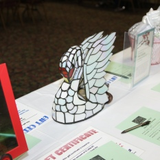Silent auction table with stained glass white swan on it