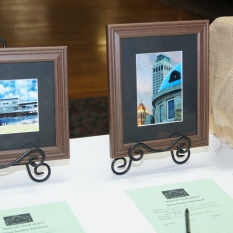 Silent auction table with framed pictures on it