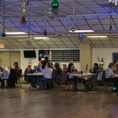 Venue with tables, Christas decors and blue chistmas lights handing from the ceiling